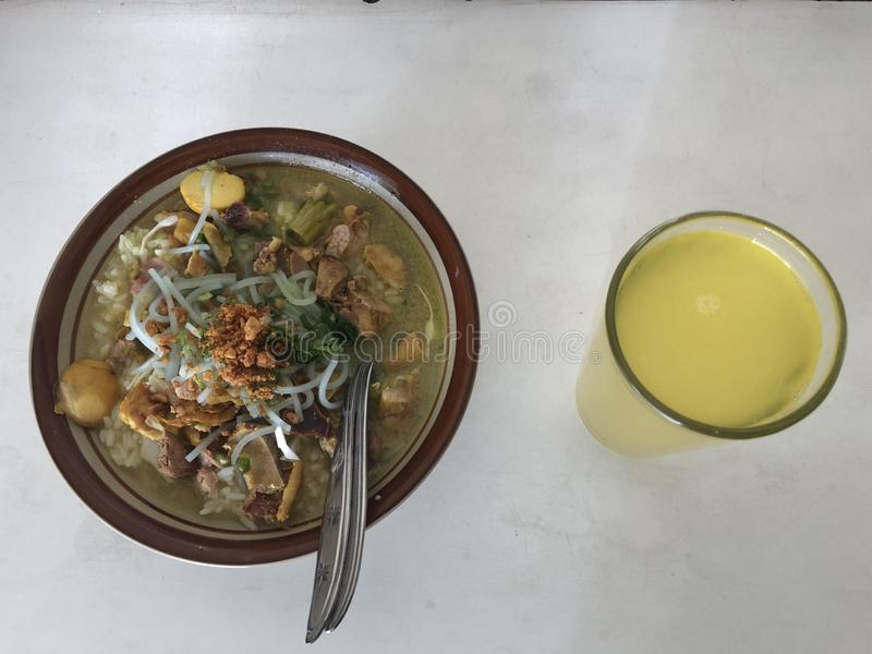 Soto ayam Lamongan or Lamongan chicken soup. Indonesia traditional chicken soup serve with egg and orange juice royalty free stock photo