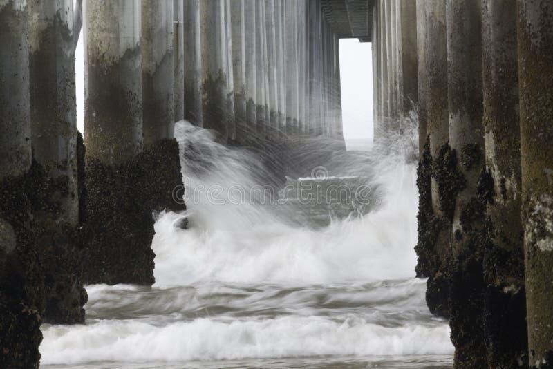 Sotto il pilastro Spruzzatura dell'acqua dall'oceano fotografie stock