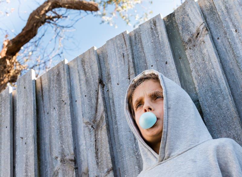 Sotto il punto di vista ad angolo dell'adolescente che soffia di gomma da masticare blu immagine stock