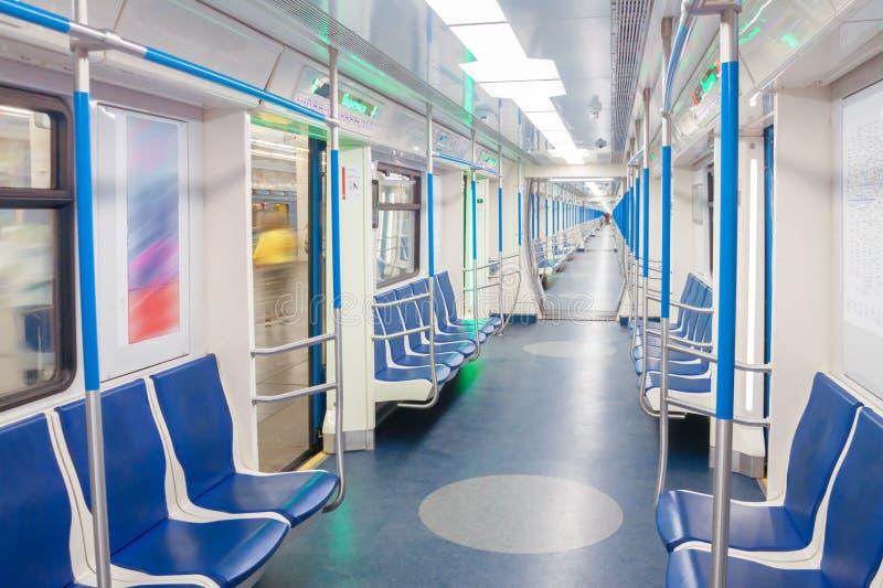 Sottopassaggio del treno di automobile con i sedili blu dentro l'interno leggero con le linee semplici di prospettiva immagini stock libere da diritti