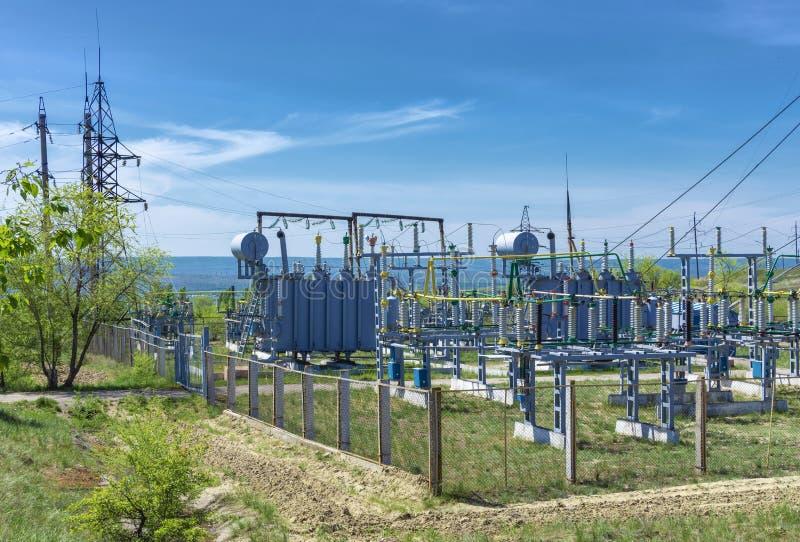 Sottostazione del trasformatore di distribuzione elettrica, contro lo sfondo di vegetazione verde fotografia stock