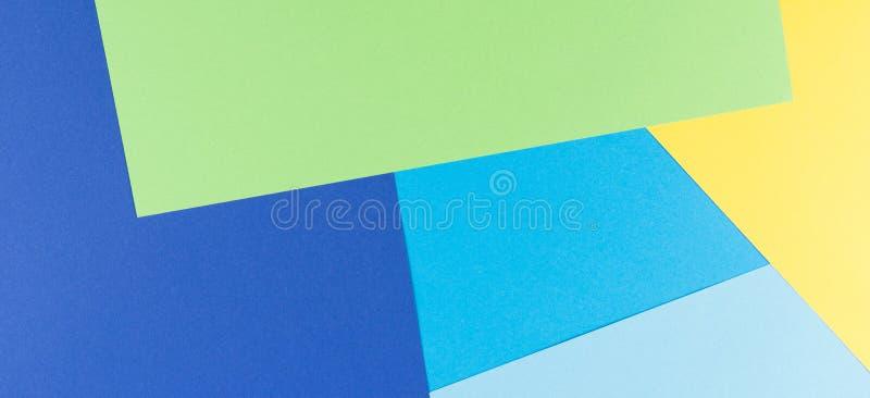 Sottragga il fondo dell'insegna della carta colorata con i toni gialli, verdi e blu fotografia stock