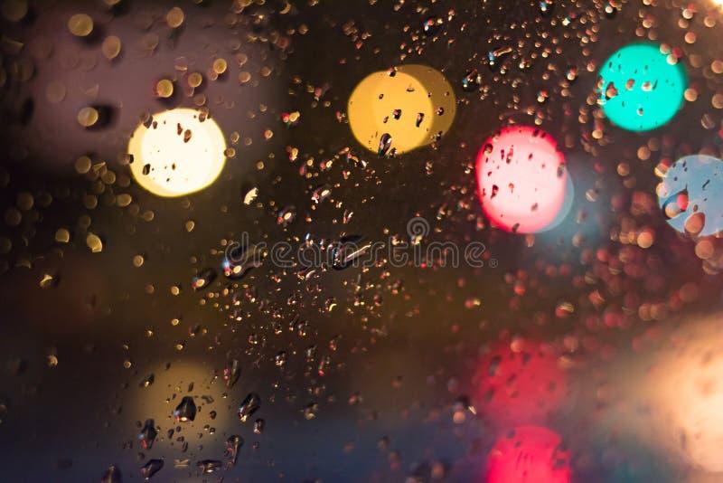 sottragga la priorità bassa Gocce sul vetro nella notte con bokeh fotografia stock libera da diritti