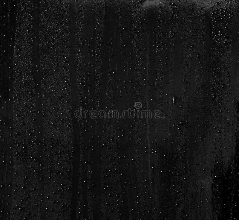 Sottragga una goccia di acqua su superficie di fondo nero brillante fotografia stock libera da diritti