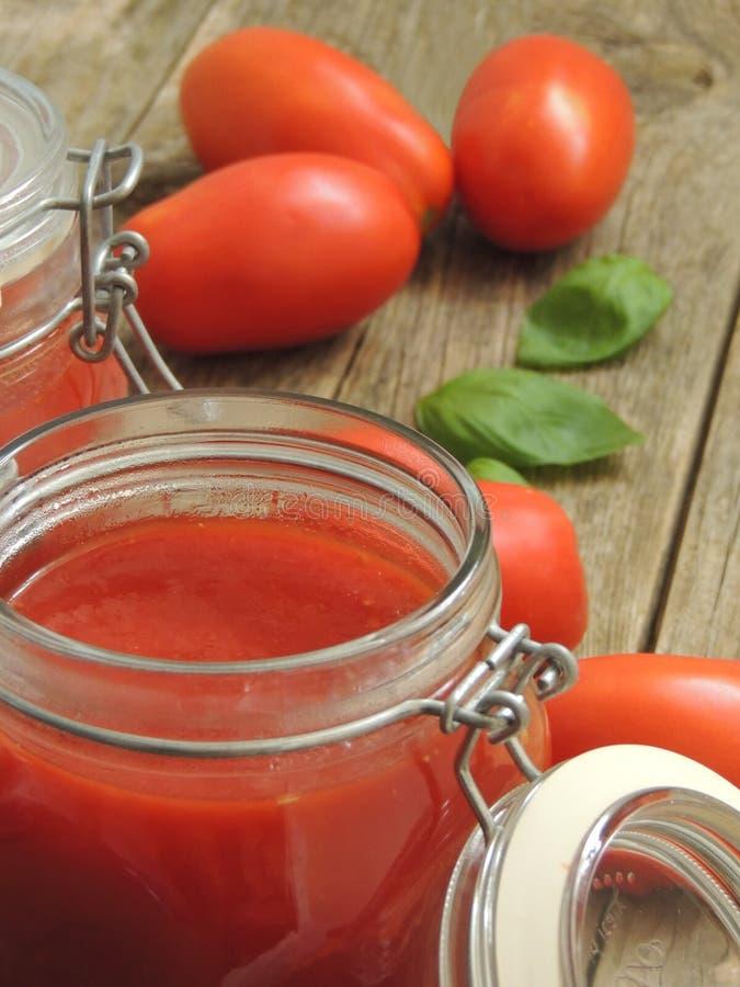 Souce fait maison de tomate avec le basilic dans un pot en verre photo stock