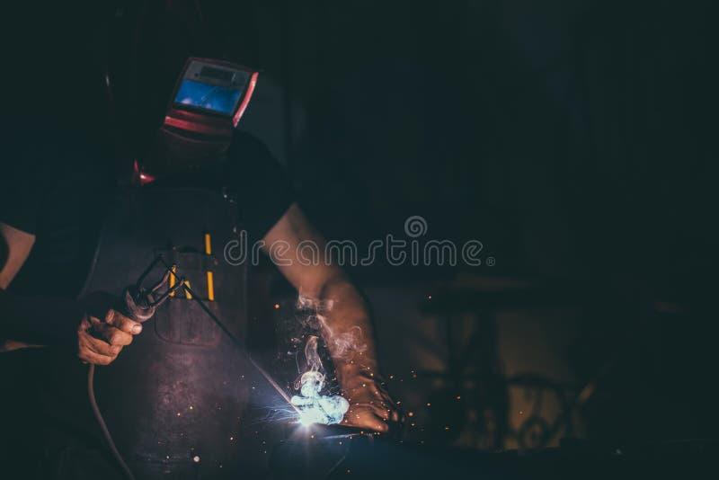Soudeur, artisan, érigeant la soudeuse en acier industrielle en acier technique dans l'usine photographie stock libre de droits