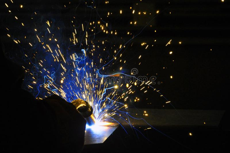 Soudeur, artisan, érigeant la soudeuse en acier industrielle en acier technique dans l'usine technique, images stock