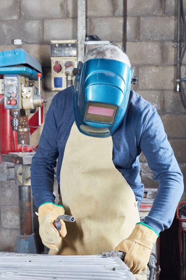 Soudeuse employant les vêtements de protection et le casque photographie stock