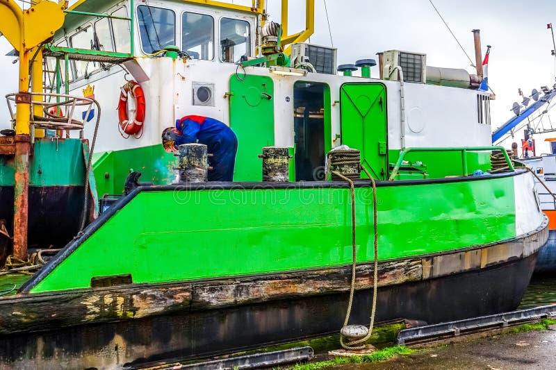 Soudeuse réparant des bornes sur un grand navire de dragueur d'aspiration de coupeur ancré pour des réparations dans Urk aux Pays photos stock