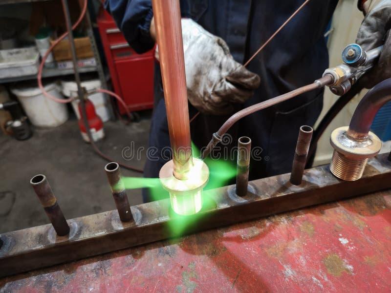 Soudure des garnitures en laiton sur le tuyau de cuivre photos stock