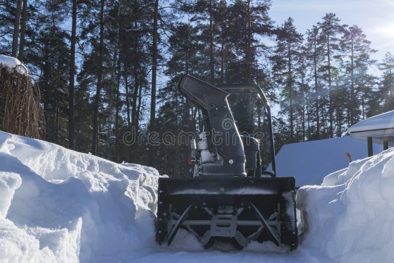 Souffleuse de neige au travail un jour d'hiver Chasse-neige enlevant la neige après tempête de neige Dégagement de la glace Machi photos stock