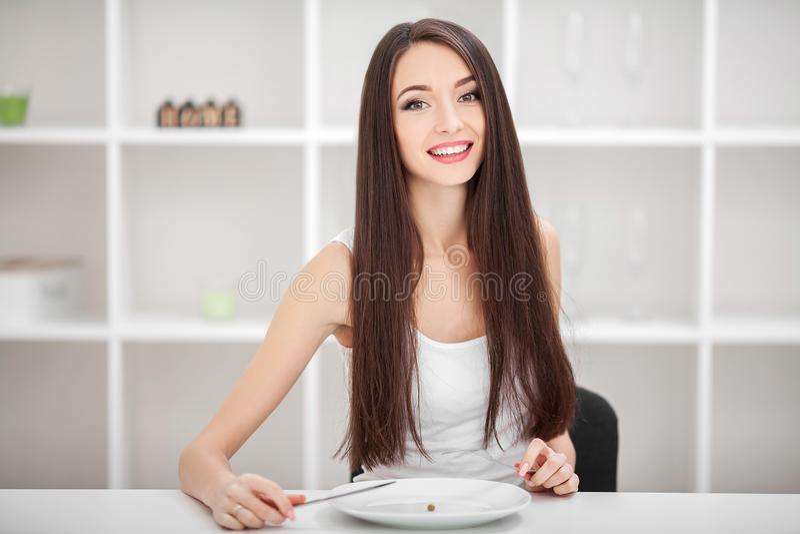 Souffrance de l'anorexie Image de fille essayant de mettre un pois sur le Th photos stock
