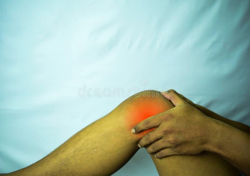 Souffrance des douleurs articulaires avec la tache rouge Mains sur la jambe comme mal de l'arthrite Concept de la maladie de geno image libre de droits