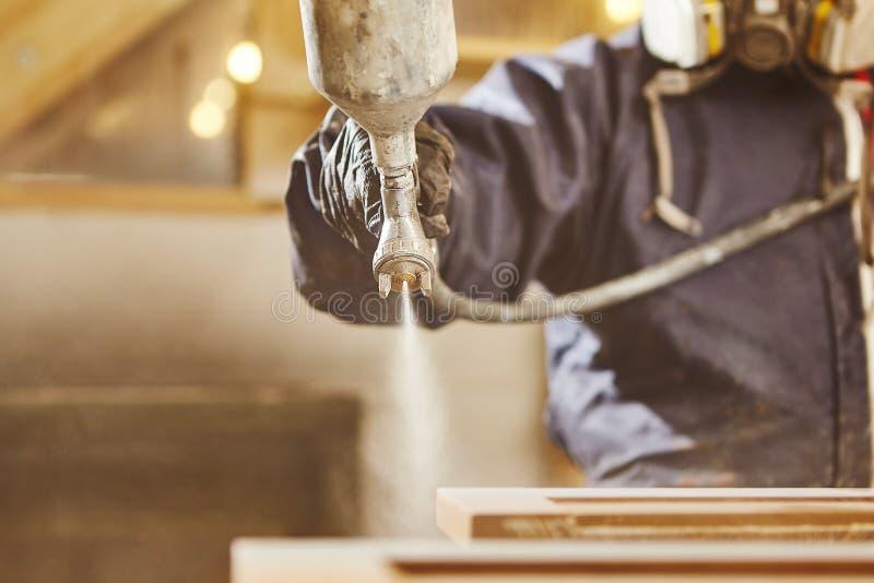 Souillure du bois avec le pistolet de pulvérisation blanc Application de lutte anti-incendie s'assurante ignifuge, dispositif de  image libre de droits