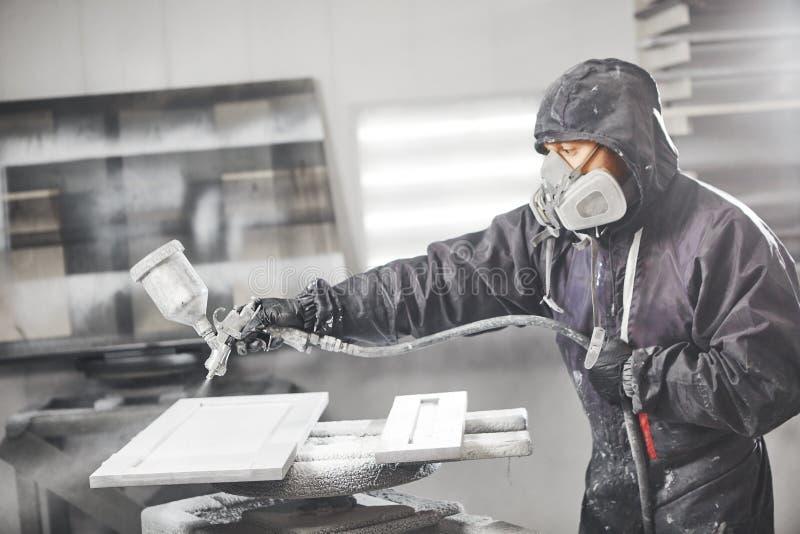 Souillure du bois avec le pistolet de pulvérisation blanc Application de lutte anti-incendie s'assurante ignifuge, dispositif de  image stock