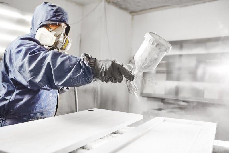 Souillure du bois avec le pistolet de pulvérisation blanc Application de lutte anti-incendie s'assurante ignifuge, dispositif de  photo libre de droits