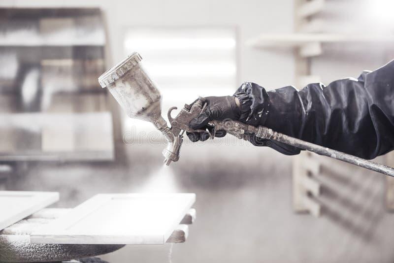 Souillure du bois avec le pistolet de pulv?risation blanc Application de lutte anti-incendie s'assurante ignifuge, dispositif de  photo stock