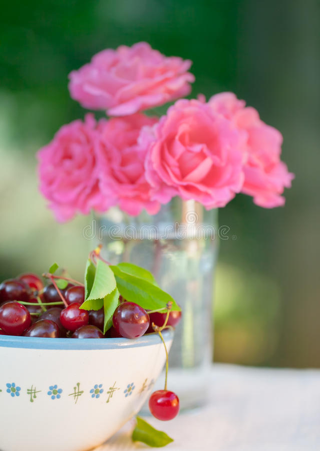 Soul cherry with roses. Soul cherry in bowl and rose bouquet in garden stock images