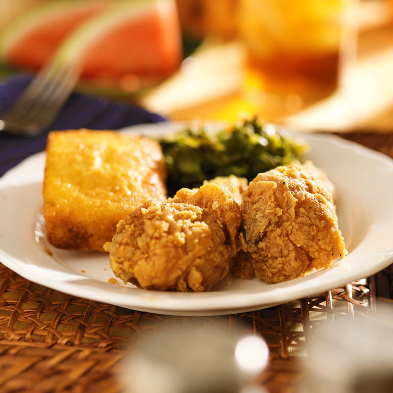 Soul food - fried chicken with collard greens and corn bread. Fried chicken with collard greens and corn bread soul food meal stock photo