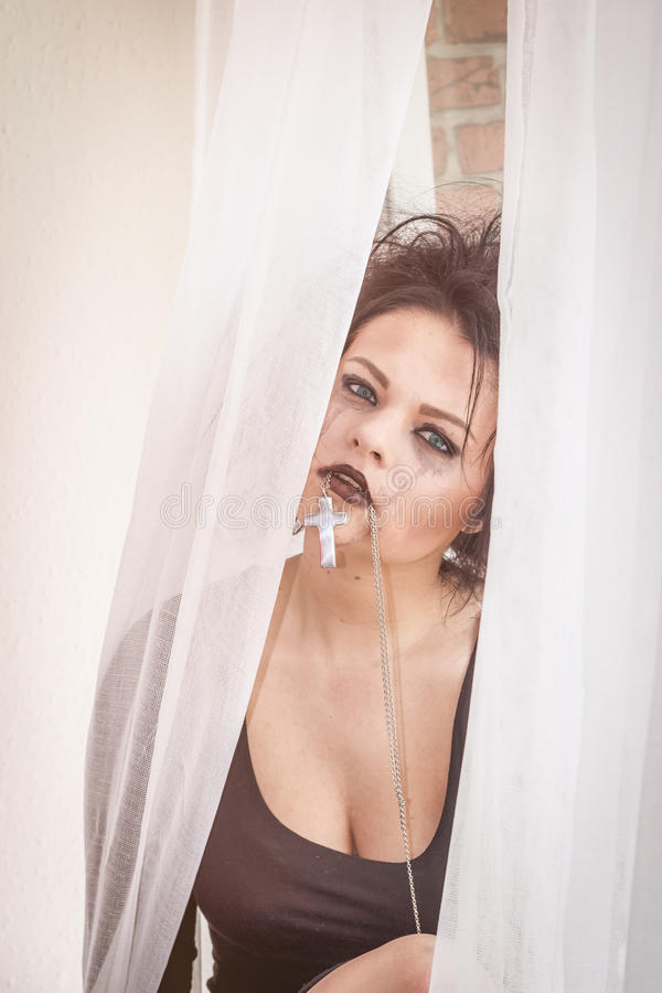 Soul pain. Beautiful rebel girl sitting in the window ,behind the curtain tear drops on her face royalty free stock images
