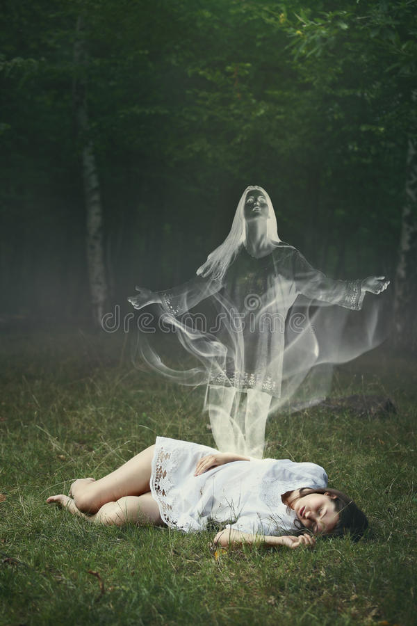 Soul of a sleeping woman in the forest. Soul of a sleeping woman leaving her body in a forest . Surreal and halloween concept