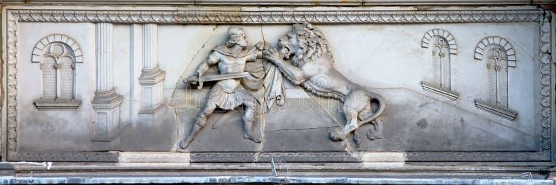 Soulagement de Bas du guerrier romain combattant un lion photos libres de droits