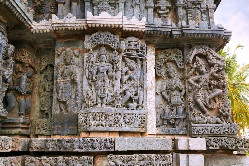 Soulagements fleuris de panneau de mur dépeignant flèche de tir gauche de Harihara, d'Arjuna aux poissons, à un drumer, et à la d photo stock