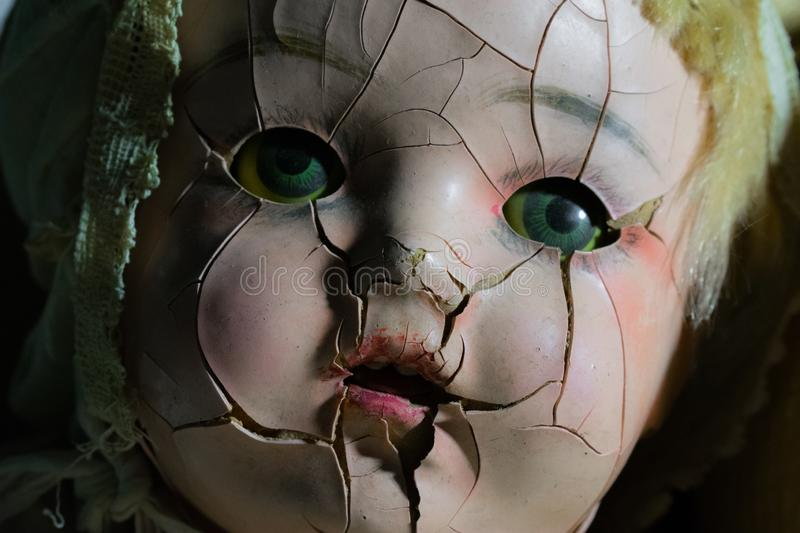 SOULlesss | Antique Baby Doll Face with Cracked Skin and Green Piercing Eyes. Antique cracked back face, close up in a dark setting with green eyes, pink cheeks stock photography
