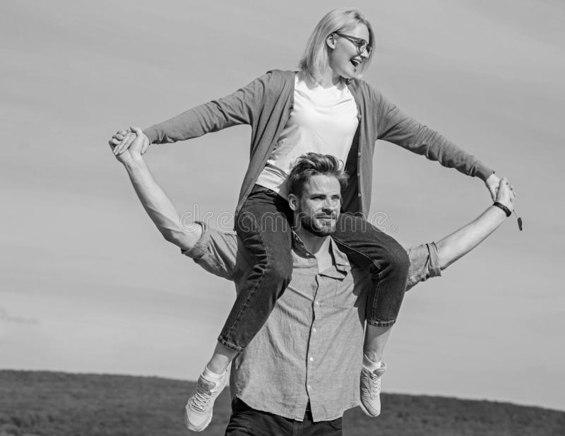 Soulmates enjoy freedom together. Couple happy date having fun together. Freedom concept. Man carries girlfriend on. Shoulders, sky background. Couple in love royalty free stock images