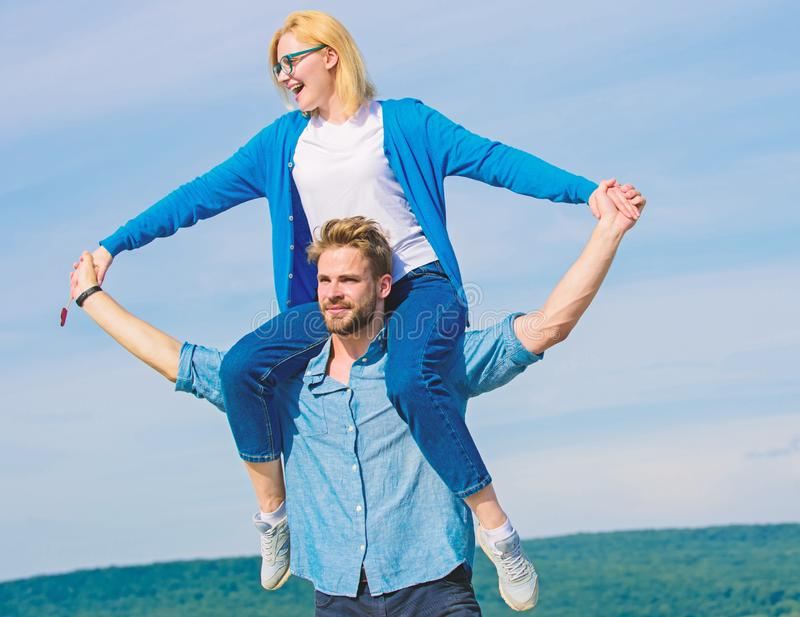 Soulmates enjoy freedom together. Couple happy date having fun together. Freedom concept. Man carries girlfriend on. Shoulders, sky background. Couple in love royalty free stock photo