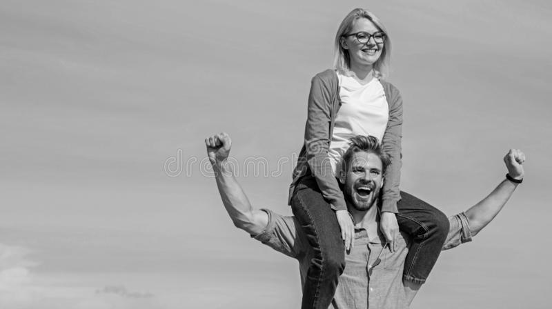 Soulmates enjoy freedom together. Couple in love enjoy freedom outdoor sunny day. Man carries girlfriend on shoulders. Sky background. Couple happy date having stock images