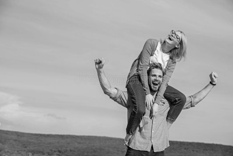 Soulmates enjoy freedom together. Man carries girlfriend on shoulders, sky background. Couple happy date having fun. Together. Freedom concept. Couple in love royalty free stock photo