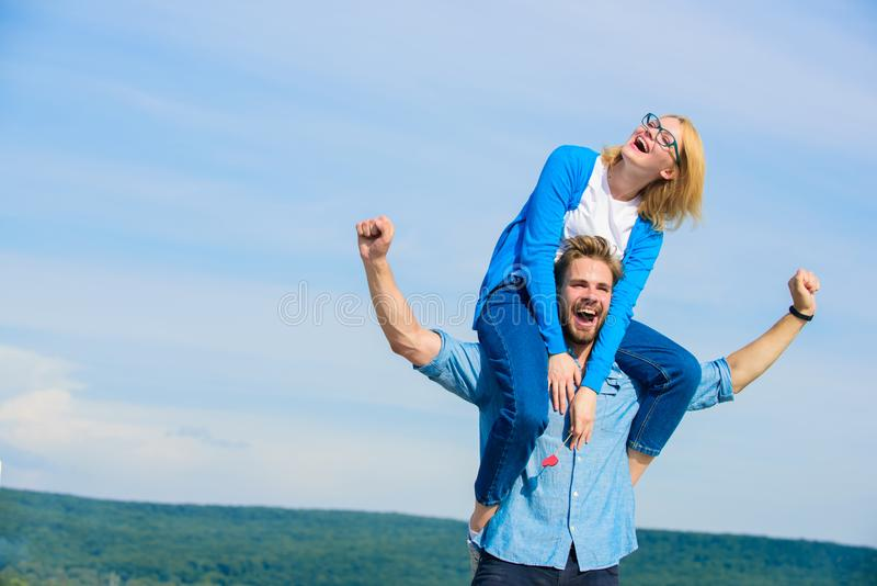 Soulmates enjoy freedom together. Man carries girlfriend on shoulders, sky background. Couple happy date having fun. Together. Freedom concept. Couple in love stock photos