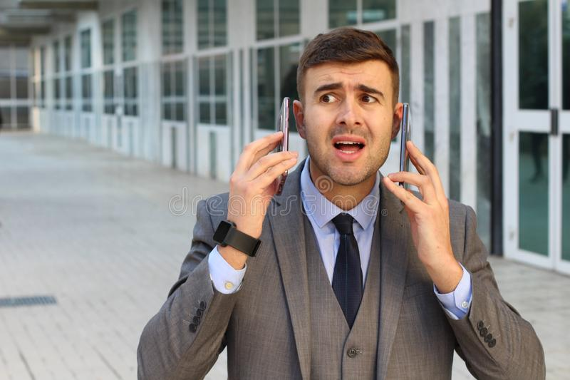 Soumettez à une contrainte l'homme d'affaires avec deux téléphones portables actifs photographie stock libre de droits