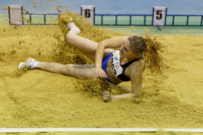 SOUMI, UKRAINE - 17 FÉVRIER 2017 : Atterrissage de Kateryna Heiko dans le bac à sable dans le concours de long saut dans le penta photos stock