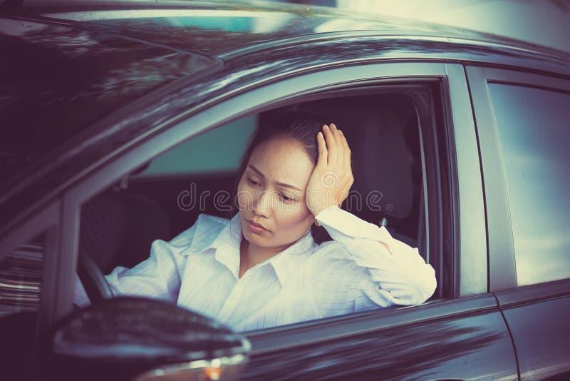 Soumis à une contrainte du conducteur asiatique de femme se reposant à l'intérieur de sa voiture photographie stock