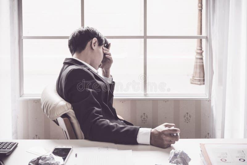 Soumis à une contrainte un homme d'affaires tient sa tête image stock