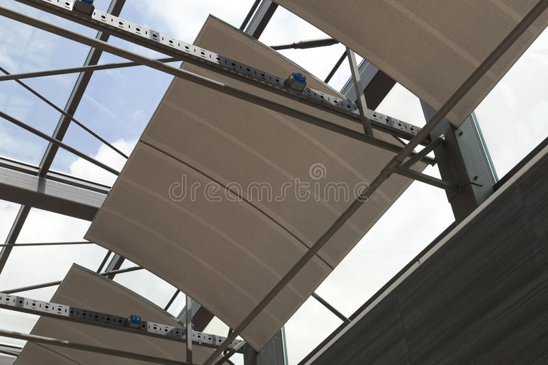 Sound absorber cloud made in Slovenia. Sound absorber cloud ceiling under glass roof in a concert hall suspended stock image