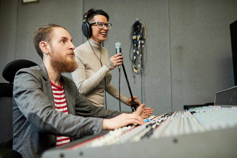 Sound designer and singer recording song in production studio stock image