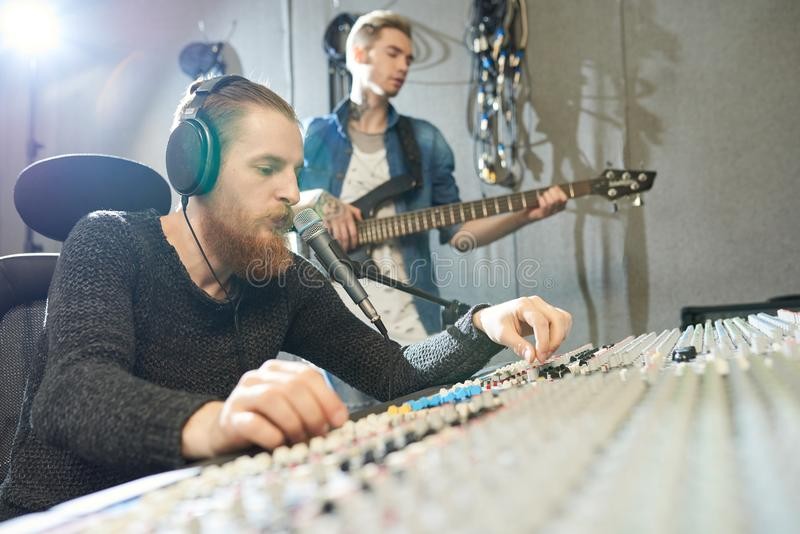 Sound engineer recording guitar performance in studio stock images