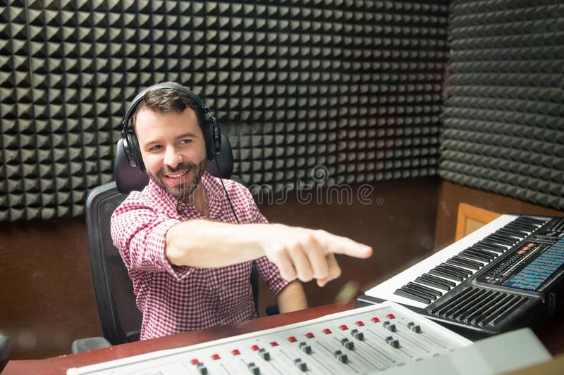 Sound engineer signaling to begin the show. Sound engineer indicating with the finger to start the show at radio station royalty free stock photography