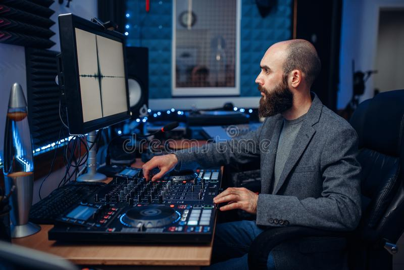 Sound engineer working in the recording studio. Sound engineer working at the remote control panel in the recording studio. Musician at the mixer, professional stock photo