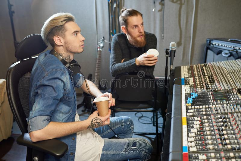 Sound engineers with coffee working in recording studio royalty free stock photography