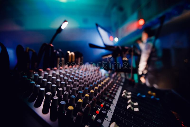 Sound equipment DJ console. Background blurred. Blue and purple colors, bright lit spotlight royalty free stock images