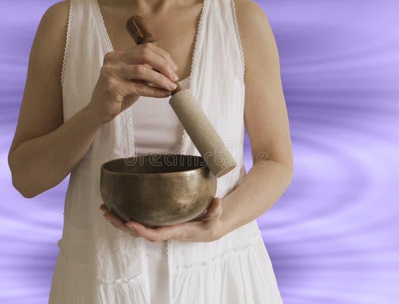 Sound Healer. Female sound healing therapist holding tibetan singing bowl with sound waves in background stock photos