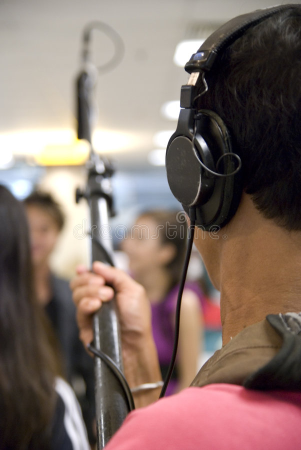 Sound man. A sound man holds up a mic while filming is in progress stock image