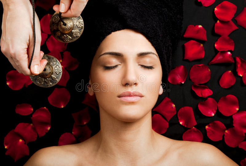 Sound massage. Close-up of beautiful female receiving energy sound massage at spa royalty free stock photo