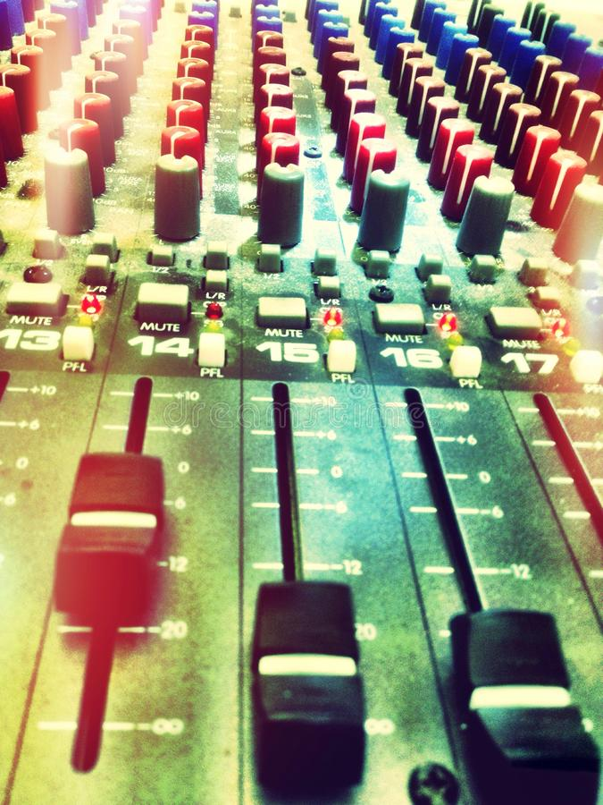 A sound mixing desk. A mixing desk has dials, knobs and switches allowing you to amplify or quieten sounds heard by an audience stock image