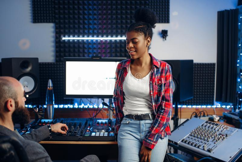 Sound operator and female performer in studio. Sound operator and female performer in headphones listens composition in recording studio. Professional audio and royalty free stock photos