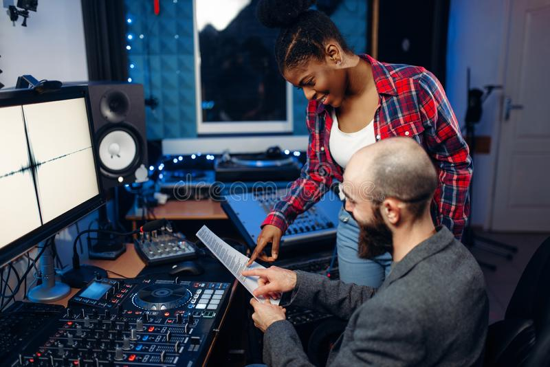 Sound operator and female singer, recording studio. Sound operator and female singer at remote control panel in audio recording studio. Musician at the mixer stock photo